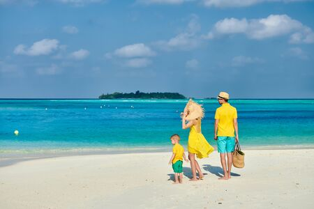 Family on beach, young couple in yellow with three year old boy. Summer vacation at Maldives. Imagens