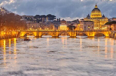 St. Peter's cathedral and Tiber river with high water at evening. Saint Peter Basilica in Vatican city with Saint Angelo Bridge in Rome, Italy