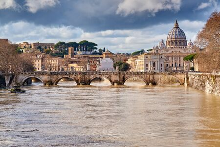 St. Peters cathedral and Tiber river with high water in February. Saint Peter Basilica in Vatican city with Saint Angelo Bridge in Rome, Italy Zdjęcie Seryjne