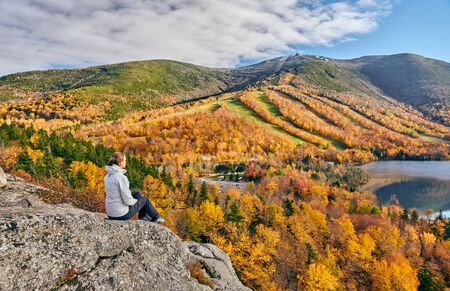 Woman hiking at Artist's Bluff in autumn. View of Echo Lake. Fall colours in Franconia Notch State Park. White Mountain National Forest, New Hampshire, USA Zdjęcie Seryjne - 128906568