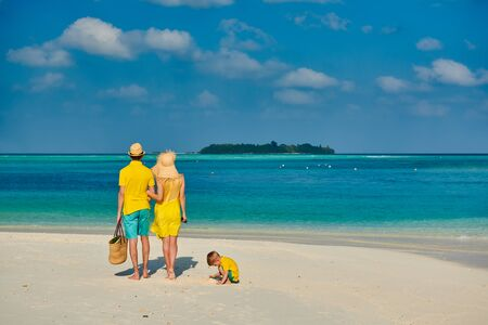 Family on beach, young couple in yellow with three year old boy. Summer vacation at Maldives. Zdjęcie Seryjne - 128907139