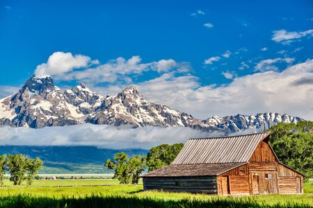 Old mormon barn in Grand Teton Mountains with low clouds. Grand Teton National Park, Wyoming, USA. Stock Photo