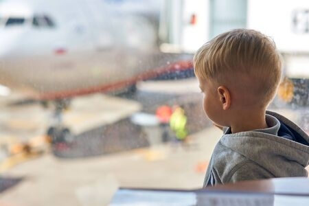 Two year old boy at the airport looking at plane