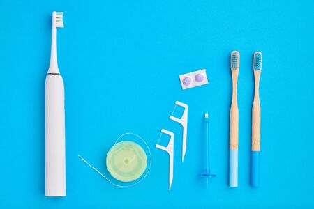 Toothbrushes and oral care tools over blue background top view copy space flat lay. Tooth care, dental hygiene and health concept.