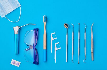 Dentist tools over blue background top view flat lay. Tooth care, dental hygiene and health concept.