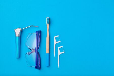 Dentist tools over blue background top view copy space flat lay. Tooth care, dental hygiene and health concept.