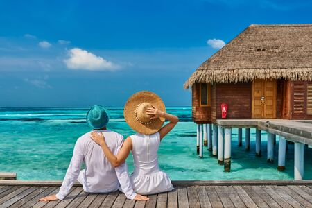 Couple in white on a tropical beach jetty near water villa at Maldives