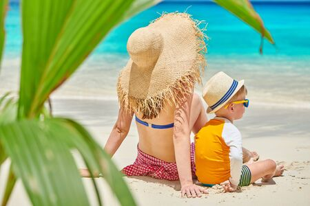 Three year old toddler boy on beach with mother. Summer family vacation at at Seychelles, Mahe.
