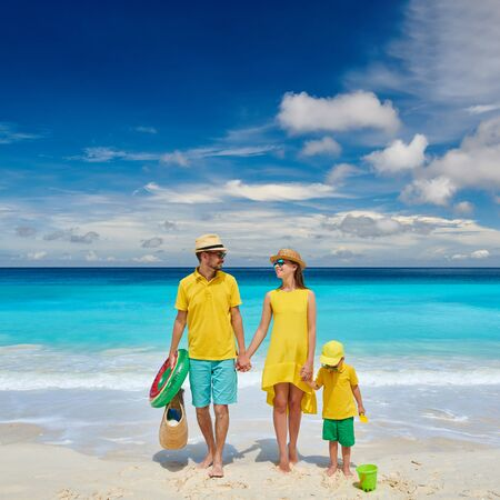 Family on beautiful Petite Anse beach, young couple in yellow with three year old toddler boy. Summer vacation at Seychelles, Mahe.