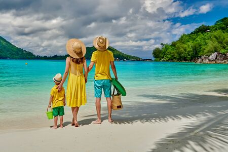 Family on beach, young couple in yellow with three year old boy. Summer vacation at Seychelles. Port Launay, Mahe.  版權商用圖片