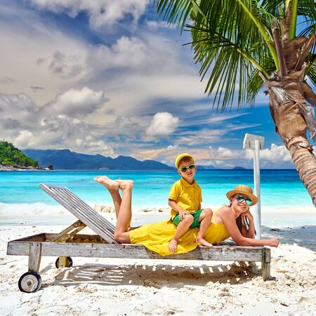 Family on beautiful Petite Anse beach, mother with three year old toddler boy on sun bed. Summer vacation at Seychelles, Mahe. Standard-Bild