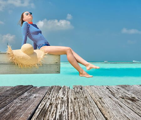 Woman sitting on wooden beach jetty. Summer vacation at Maldives.