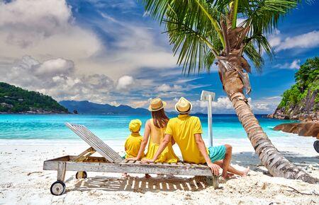 Familie am schönen Strand Petite Anse, junges Paar mit drei Jahre altem Kleinkindjungen, der auf Sonnenliege sitzt. Sommerurlaub auf den Seychellen, Mahe.