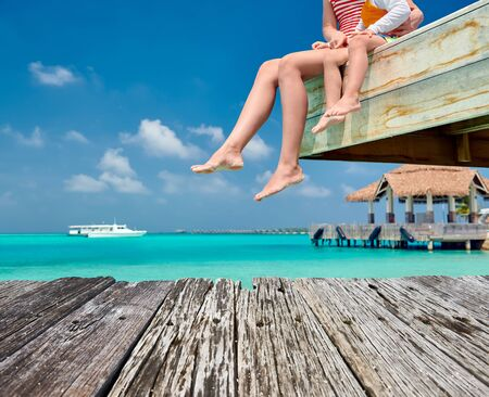 Three year old toddler boy with mother sitting on wooden jetty. Summer family vacation at Maldives.