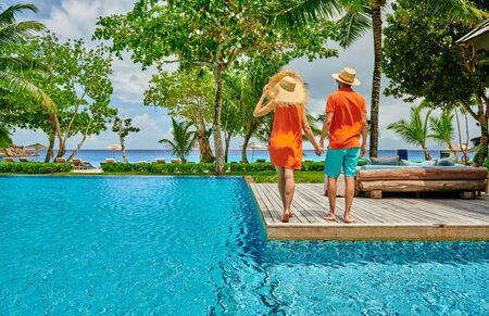 Young couple by poolside. Resort swimming pool at Mahe, Seychelles. Standard-Bild