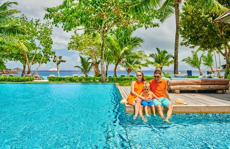 Family by poolside, young couple with three year old toddler boy. Resort swimming pool at Mahe, Seychelles. Standard-Bild