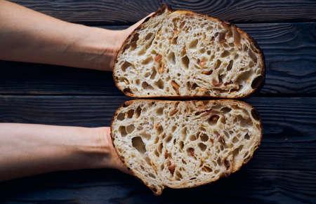 Freshly baked homemade tartine bread in woman's hands Imagens