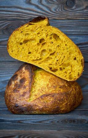 Freshly baked homemade tartine bread with turmeric on dark wooden table Imagens