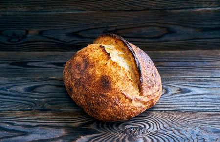 Freshly baked homemade tartine bread on dark wooden table