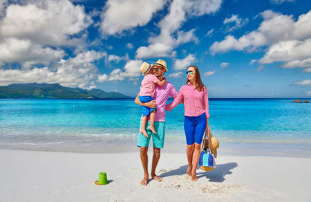 Family on beautiful Anse Soleil beach, young couple with three year old toddler boy. Summer vacation at Seychelles, Mahe.