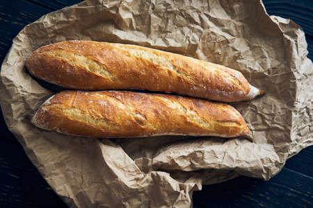 Freshly baked homemade baguette bread on dark wooden table