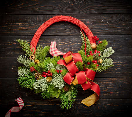 Christmas wreath and candles on dark rustic wooden background