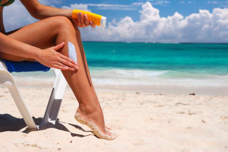 Tan woman applying sun protection lotion