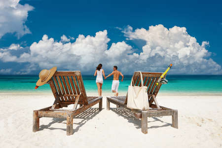 Couple in white running relax on a tropical beach at Maldives