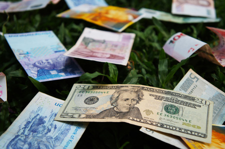 two us dollar: Stack of various banknotes on green lawns