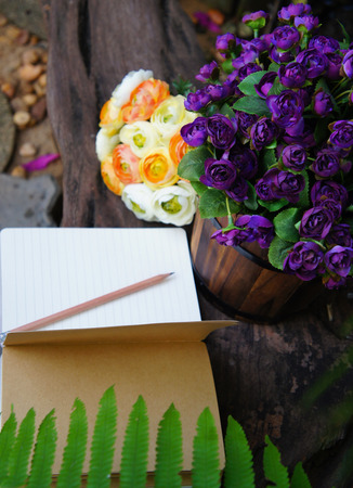 Artificial purple and yellow roses with an open note book photo