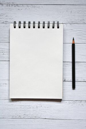 Clear sheet note book and black pencil on white wood background. Zdjęcie Seryjne