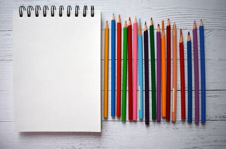 Note for drawing and colour pencils on white wood background.