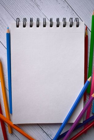 Clear sheet note and colour pencils on white wood background.