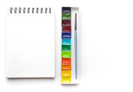Clear sheet note book and colour watercolor paint on white background.