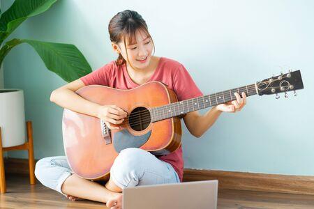 Junge Asiatin, die zu Hause Gitarre lernt