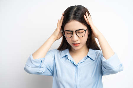 portrait of asian woman holding her head because of a headache Foto de archivo