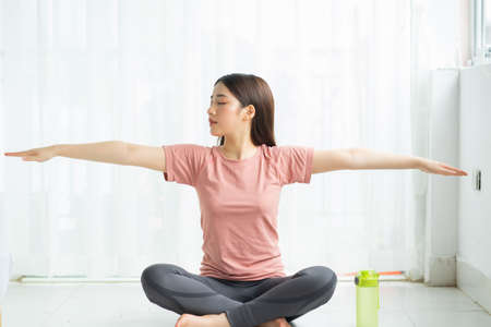 portrait of asian woman practicing yoga at home