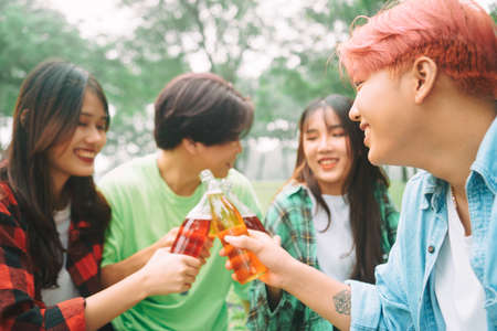 Group of young Asians happily drinking beer at a picnic at the park