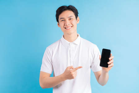 Smiling young man holds a modern smartphone in his hand and shows his finger on a blank white screen, isolated on a blue background. Foto de archivo