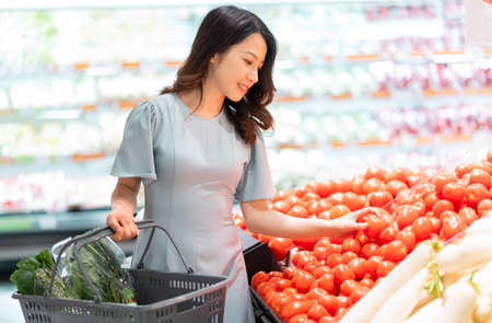 The young girl is choosing to buy vegetables at the supermarket Stockfoto