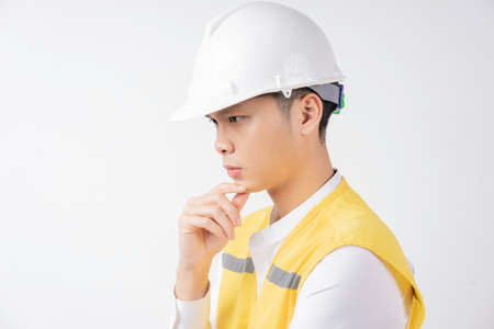 Portrait of male construction engineer thinking on white background