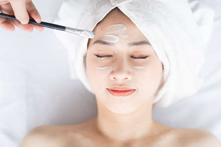 Asian woman doing beauty treatments, spa treatments and being applied cream to her face