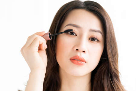 Asian woman sitting makeup in front of mirror