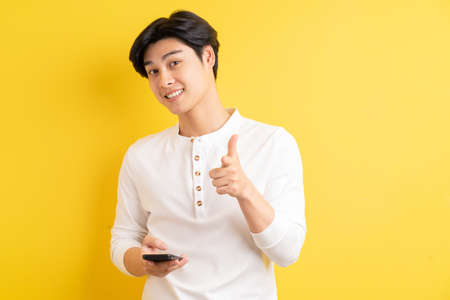 Asian man using his phone and pointing outwards on a yellow background