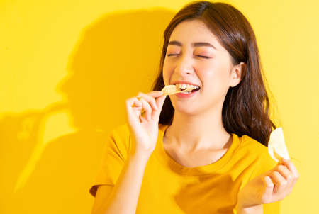 Young Asian girl eating snack on yellow background