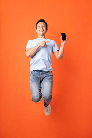 Asian businessman jumping and holding smartphone