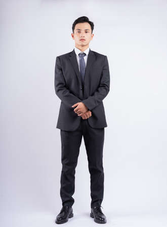 Young Asian businessman standing on white background