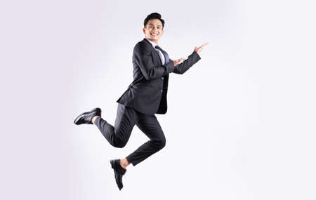 Young Asian businessman jumping on white background