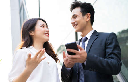 Two Asian business people using smartphone and talking together