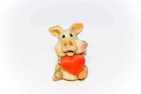 Stone figure of the pig holding red heart Stock Photo